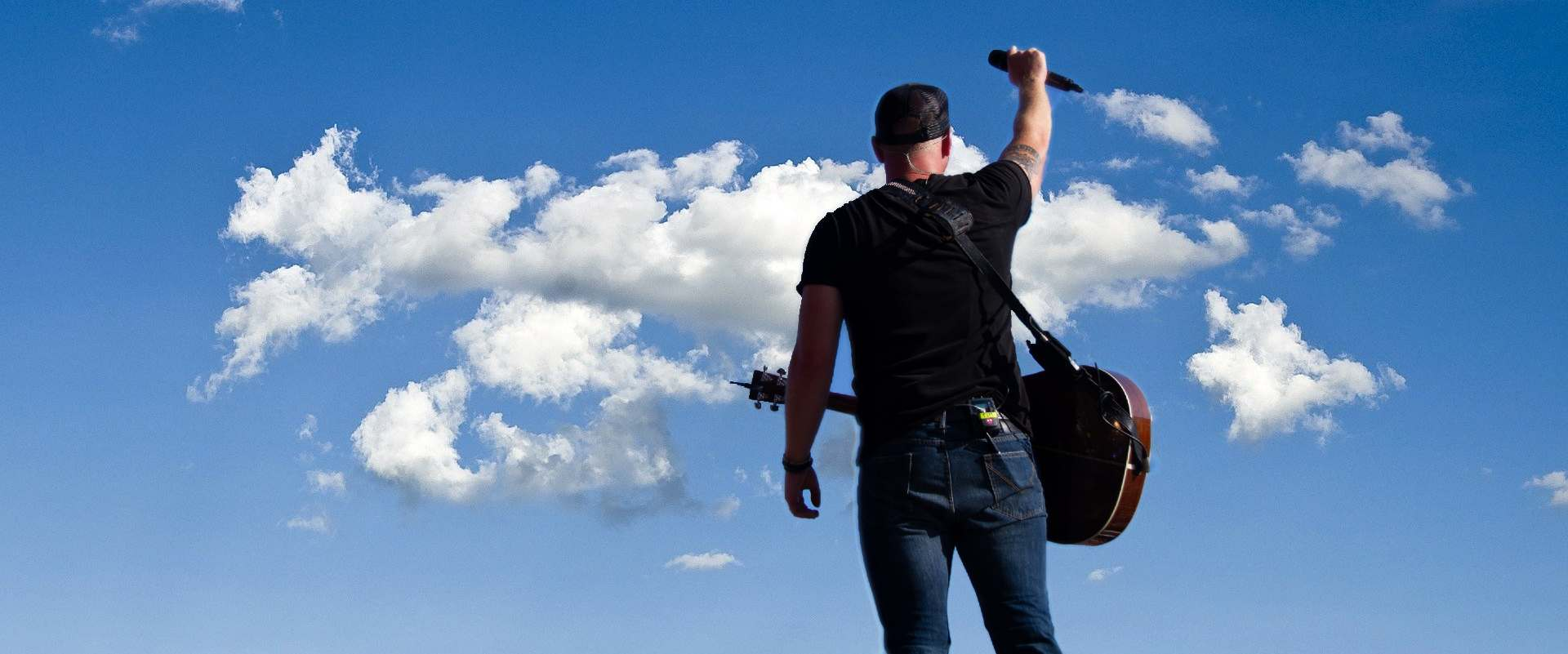 Tim Hicks on stage in front of clouds